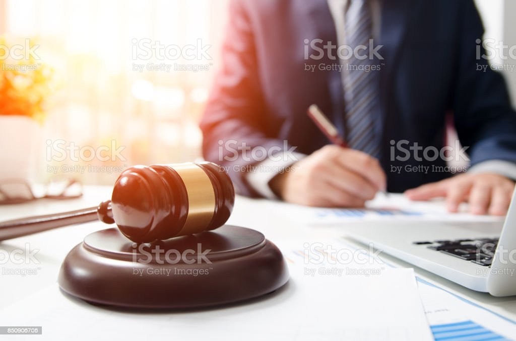 Wooden gavel on table. Attorney working in courtroom. stock photo