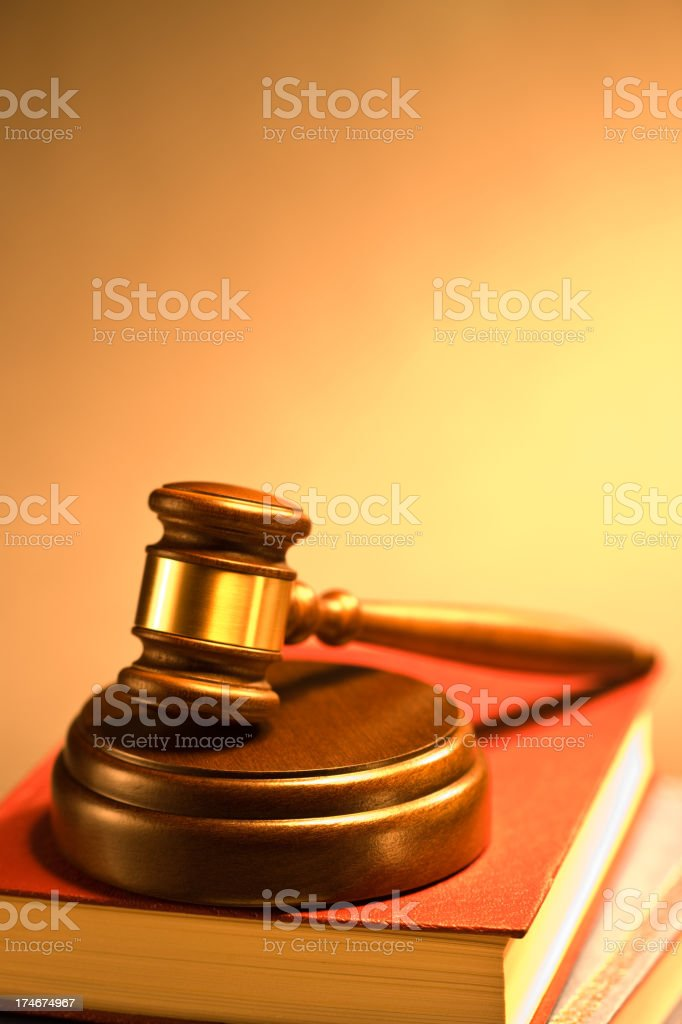 Wooden gavel placed on a stack of books royalty-free stock photo