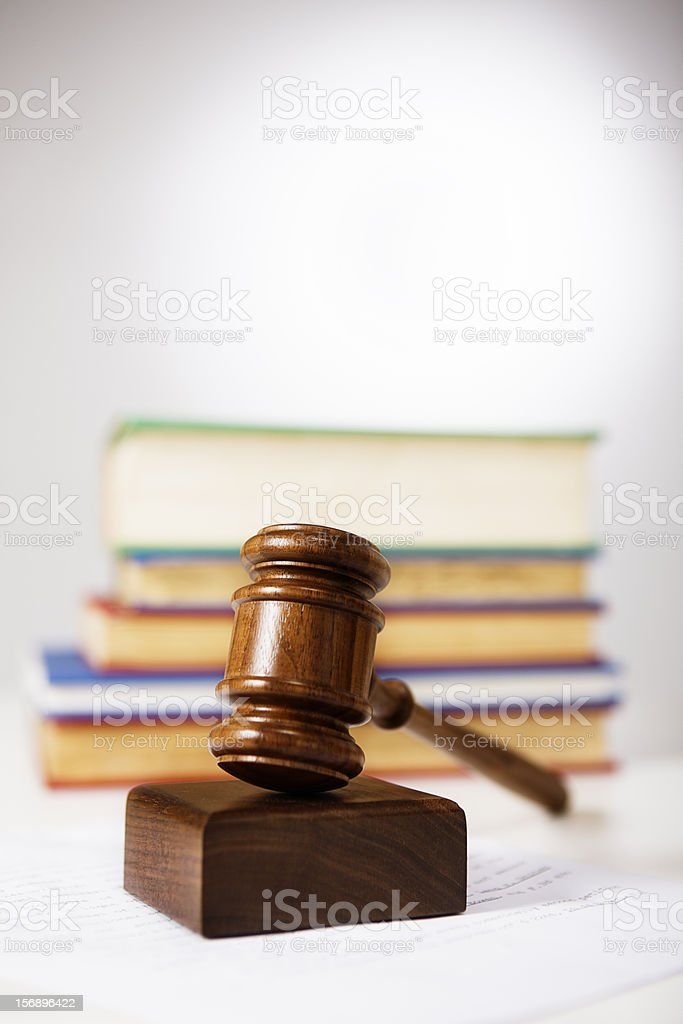 Wooden gavel, sounding block and law books: justice in action royalty-free stock photo