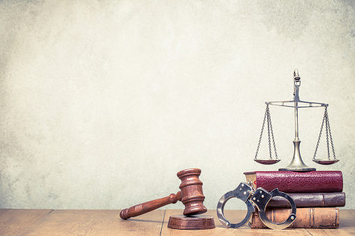 istock Wooden gavel, Vintage law scales, handcuffs and books on the desk front concrete wall background. Symbols of justice still life. Retro old style filtered photo 1044373974