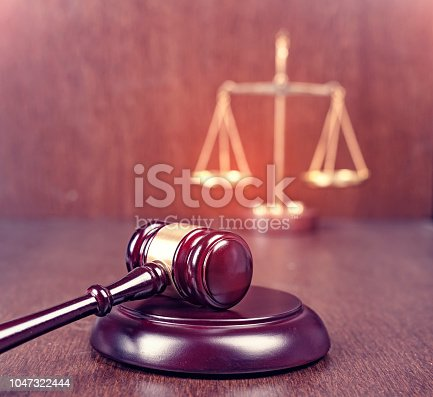 istock Wooden gavel with scales on wooden table 1047322444