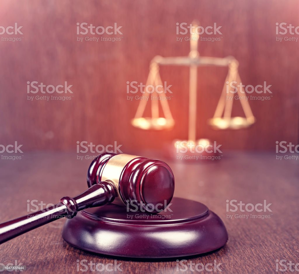 Wooden gavel with scales on wooden table stock photo