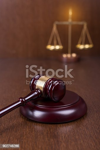 istock Wooden gavel with scales on wooden table 902746286
