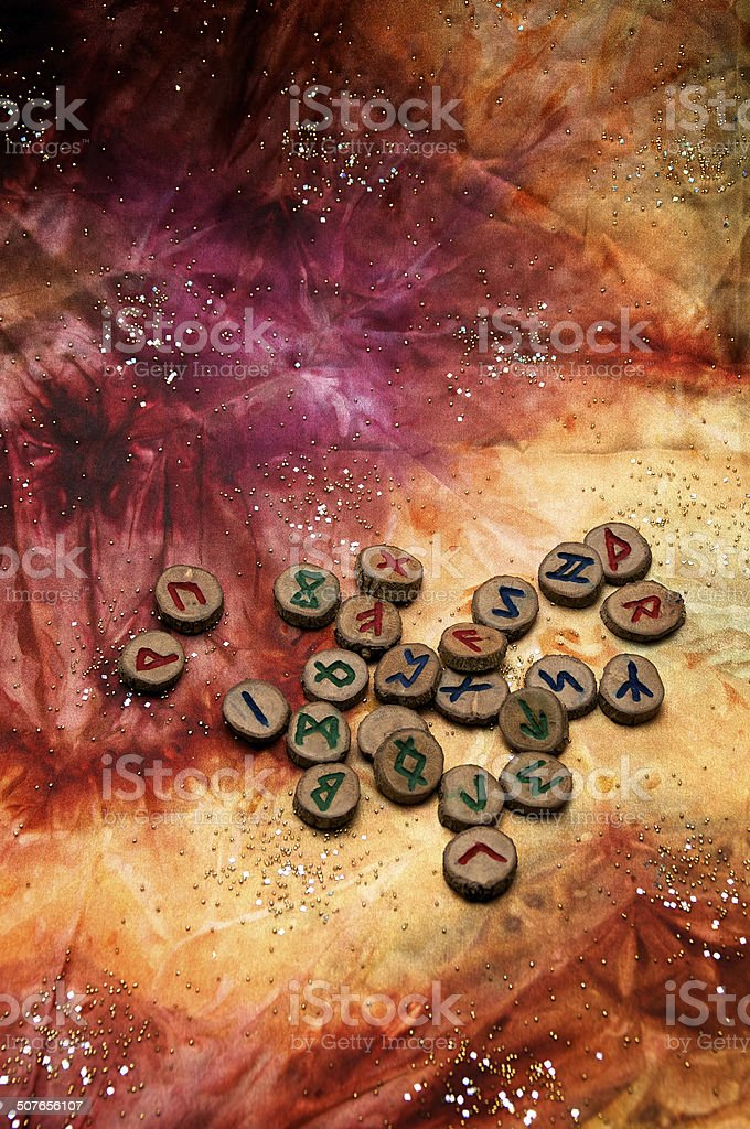 wooden german futhark runes on colorful mystical cloth stock photo