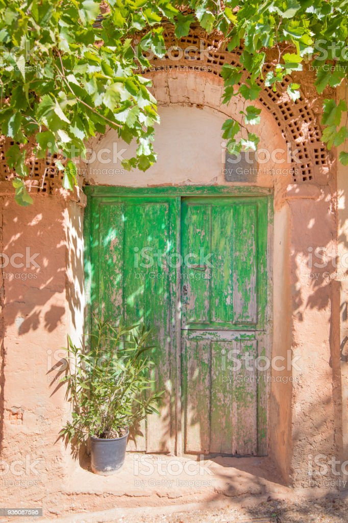 wooden green door of house built with bricks and adobe stock photo
