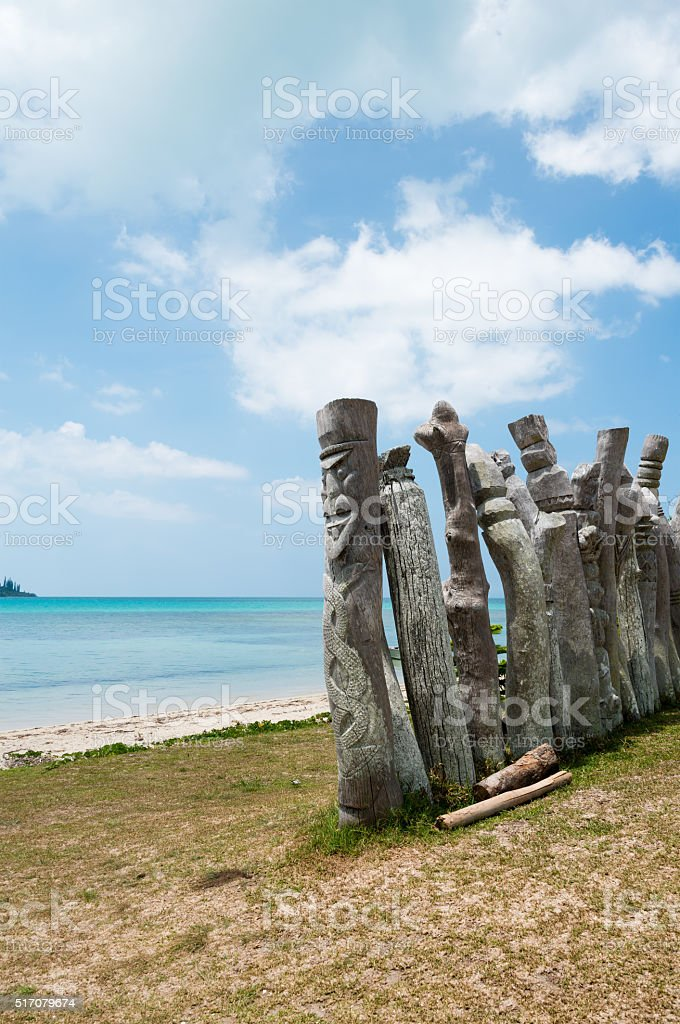 Wooden guardians on the beach stock photo