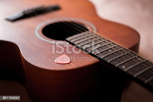 1014432572istockphoto Wooden guitar with lighting on the body to show texture of guitar and pick 951154042