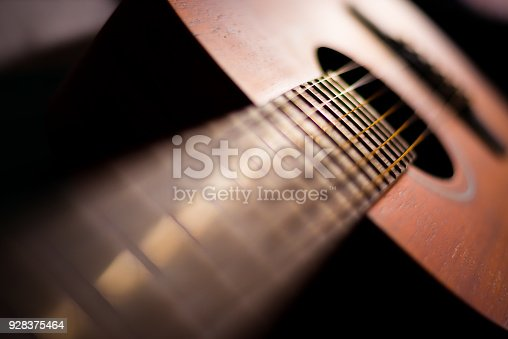 1014432572 istock photo Wooden guitar with lighting on the body to show texture of guitar 928375464