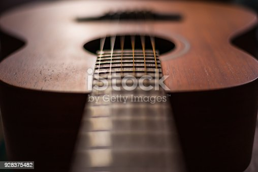 1014432572 istock photo Wooden guitar with lighting on the body to show texture of guitar 928375482