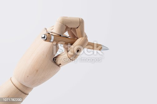 istock wooden hand hold pen isolated on white background 1071782200
