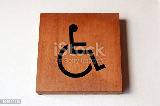 istock Wooden handicapped mark on the wall in front of the Bathroom disabled. 895972410