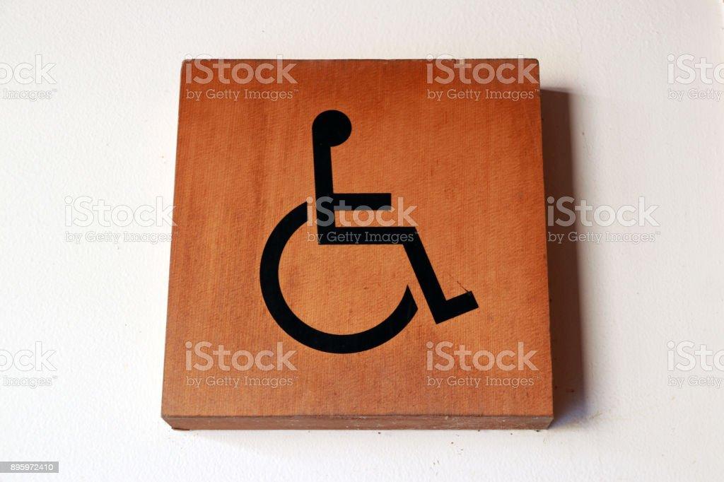 Hölzerne Behinderte markieren an der Wand vor dem Bad deaktiviert. – Foto