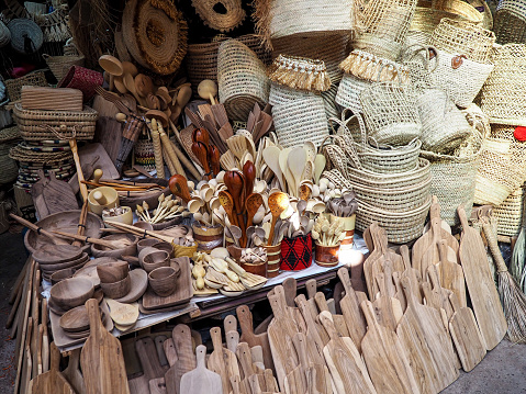 Wooden handmade bowls, spoons, boards, kitchen utensils and baskets on display at street market.