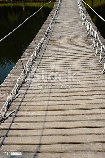 View over a wooden suspension bridge into the garden in thailand