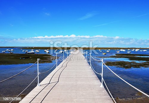 Wooden Harbour Jetty at Ria Formosa with blue sky in background  in Faro Marina, Algarve, Portugal