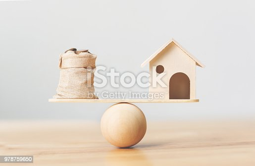 1145921132istockphoto Wooden home and coins money in bag on wood scales. Property investment and house mortgage financial real estate concept 978759650