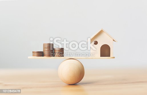 1145921132istockphoto Wooden home and money coins stack on wood scale. Property investment and house mortgage financial real estate concept 1012845478