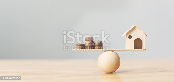 1145921132istockphoto Wooden home and money coins stack on wood scale. Property investment and house mortgage financial real estate concept 1136482657