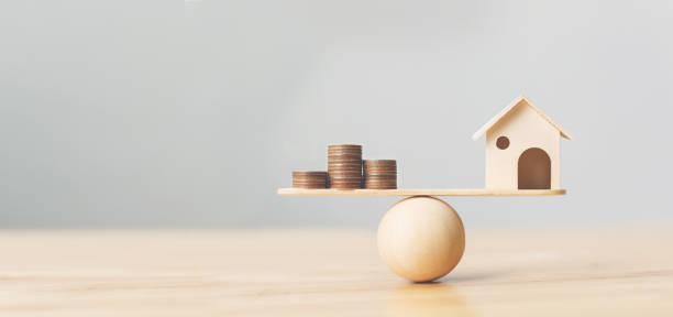holzheim-und geldmünzen stapeln sich im holzmaßstab. immobilieninvestitionen und haushypothekengeschäfte finanzimmobilienkonzept - gleichgewicht stock-fotos und bilder