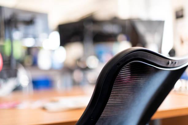 黒い椅子のクローズアップで木製の家やオフィスの部屋や職場や家でのコンピュータエレクトロニクスと空きスペースのボケの背景 - オフィスチェア ストックフォトと画像