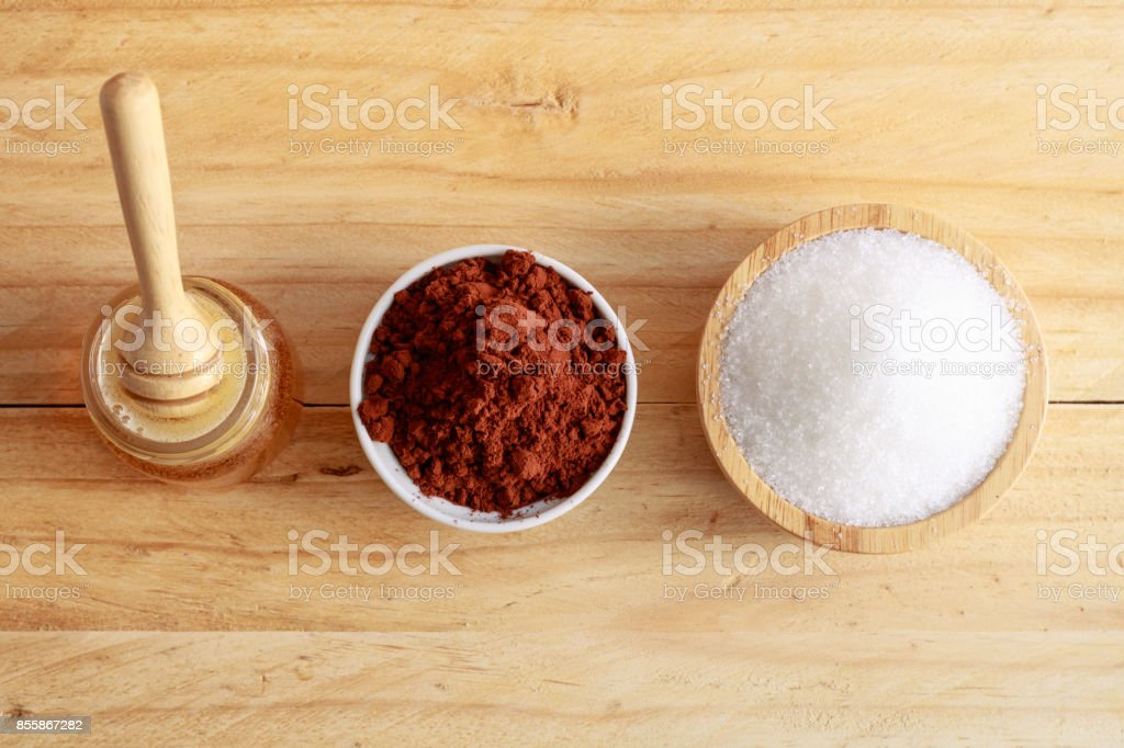 wooden honey dipper in honey bottle and sugar in wooden bowl and cocoa in ceramic bowl on wooden table, top view stock photo