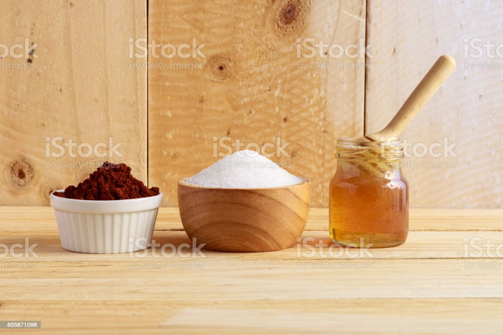 wooden honey dipper in honey bottle and sugar in wooden bowl and cocoa in ceramic bowl on wooden table stock photo