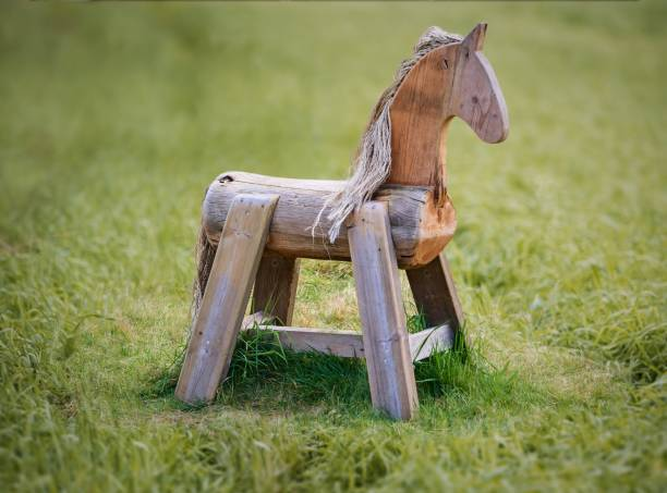 Wooden horse in the middle of grass in summer stock photo