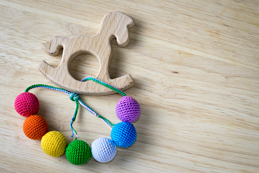 Necklace made from knitted beads and wooden horse toy for the baby sitting in a sling. Knitted beads. Sling nursing necklace.