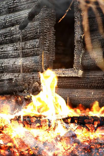 trähus efter branden. kol på stockarna. askan av huset från elden. bränd förstörd stuga. - brand sotiga fönster bildbanksfoton och bilder