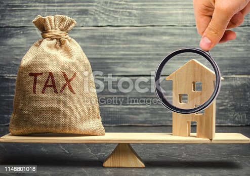 612372074 istock photo Wooden house and a money bag with the word Tax on the scales. Taxes on real estate, payment. Register of taxpayers for property. Law-abiding citizen. Evasion of payment. Court law. Debts 1148801018
