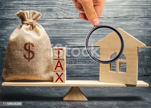612372074 istock photo Wooden house and a money bag with the word Tax on the scales. Taxes on real estate, payment. Register of taxpayers for property. Law-abiding citizen. Evasion of payment. Court law. Debts 1148809385