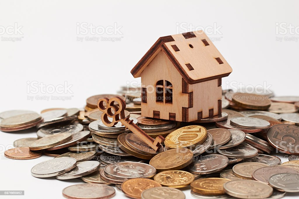 Wooden house and key on the coins. stock photo