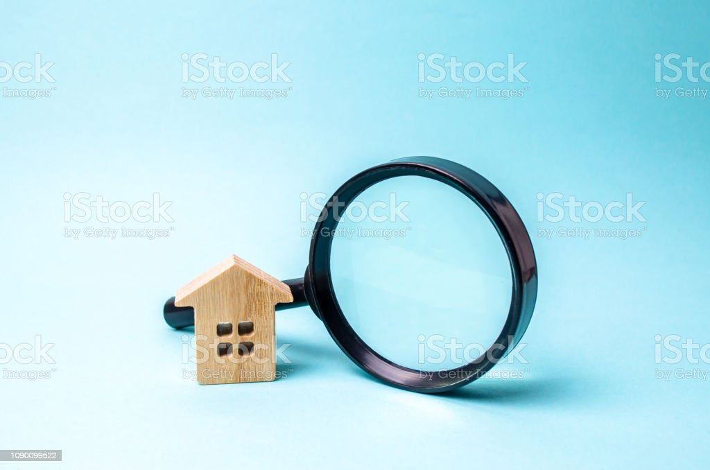 Wooden House And Magnifying Glass On A Blue Background The
