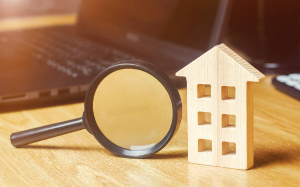 Wooden house and magnifying glass. Property valuation. Choice of location for the construction. House searching concept. Search for housing and apartments. Real estate concept. Home appraisal stock photo