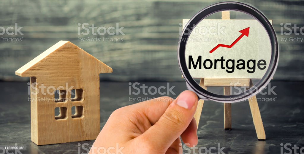 Wooden house and the inscription Mortgage and up arrow. Raising...