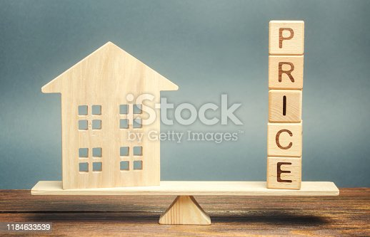915688450 istock photo Wooden house and the word Price on the scales. Fair valuation property concept. Home appraisal. Fair trade and cost. Legal transparent deal. Business and real estate 1184633539