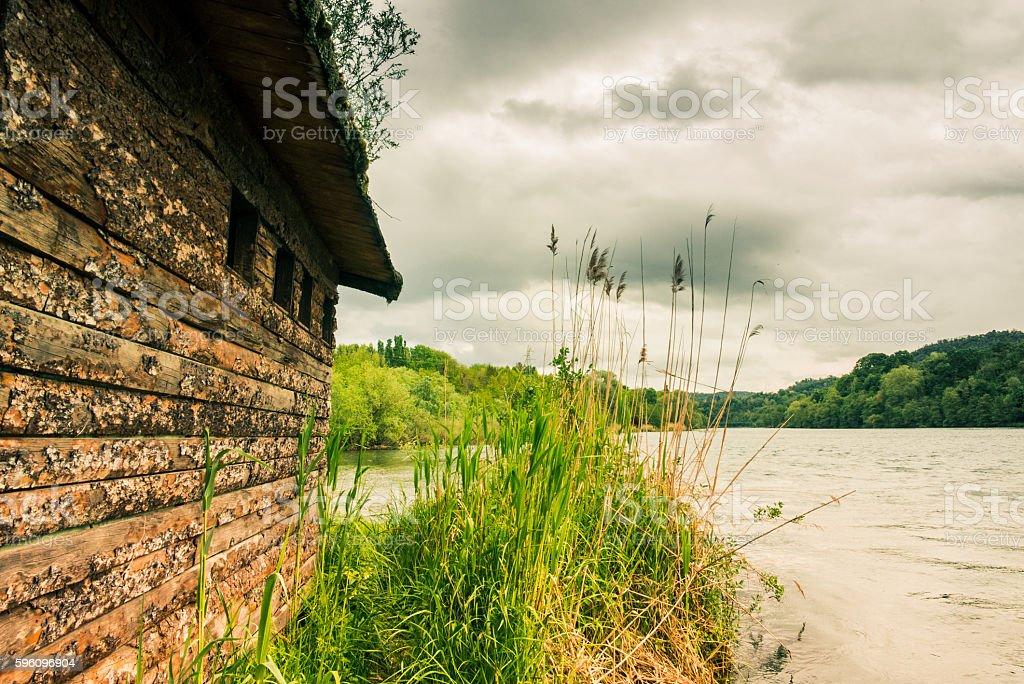 Holzhaus am Fluss in einem wolkigen Tag Lizenzfreies stock-foto