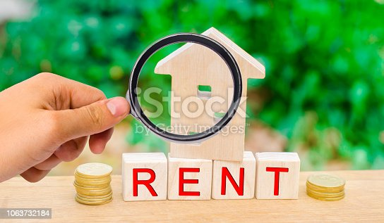 istock Wooden house, coins with the inscription rent. Rental of property, apartments. services of a realtor. affordable housing, rental prices. real estate 1063732184
