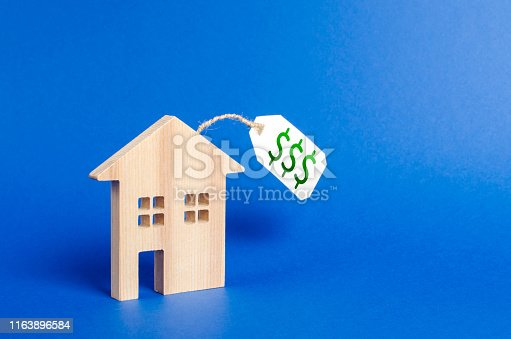 istock Wooden house figure and price tag. Selling a house or auction. Realtor Services. Buying liquid and expensive real estate and investments. housing, credit and Mortgage loans. Property valuation 1163896584