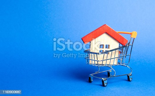 istock Wooden house in a Supermarket trading cart. The concept of buying a house or apartment. Affordable housing. Profitable and cheap loans for real estate. Buying a home. Mortgage and loan. Place for text 1163900682