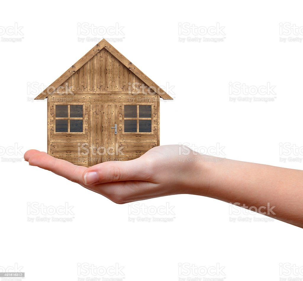 Wooden house in hand stock photo