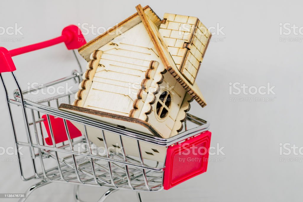 Wooden House In Toy Shopping Cart Real Estate And Financial Concept