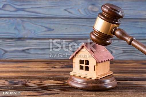 istock wooden house, judge's gavel on wooden background 1151157767