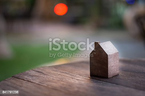 istock Wooden house model in garden with red bokeh background that seem like the sun.Wooden house model  at sunset 841791238