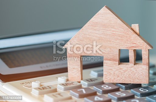 Wooden house model on calculator for budget payment or buying home. Ideas for property real estate mortgage loan or investment or planing save money for management agreement to buy new housing