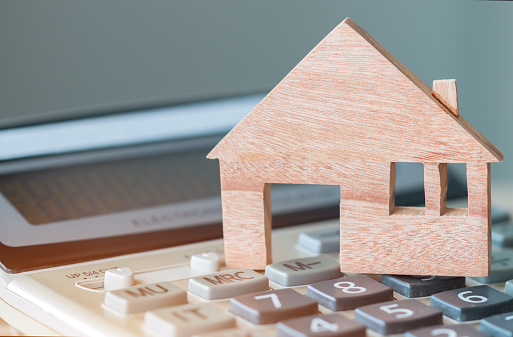 626187670 istock photo Wooden house model on calculator for budget payment or buying home. Ideas for property real estate mortgage loan or investment or planing save money for management agreement to buy new housing 1157933359