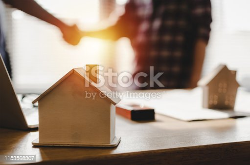 1055059750istockphoto wooden house model on workplace desk with construction worker team hands shaking greeting start up plan new project contract in office center at construction site, partnership and contractor concept 1153568307