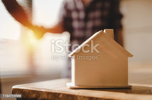 1055059750 istock photo wooden house model on workplace desk with construction worker team hands shaking greeting start up plan new project contract in office center at construction site, partnership and contractor concept 1154759369