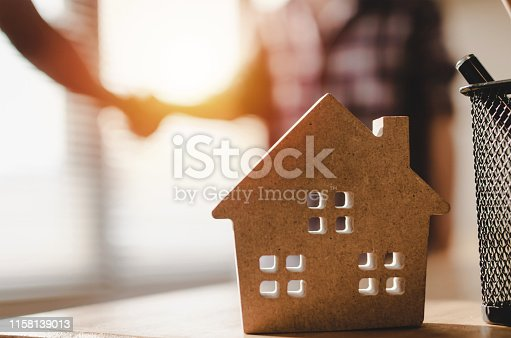 1055059750 istock photo wooden house model on workplace desk with construction worker team hands shaking greeting start up plan new project contract in office center at construction site, partnership and contractor concept 1158139013