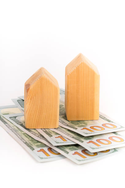 wooden house model with dollars banknotes, real estate concept wooden house model with dollars banknotes, real estate concept apparently stock pictures, royalty-free photos & images